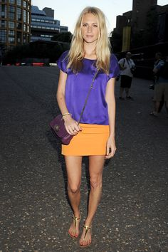 Poppy Delevingne in an orange mini-skirt, purple silk top, gold leather sandals and a purple Mulberry bag.