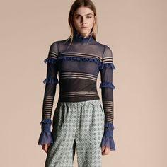 A tactile striped sweater softened by tiered ruffles from the cuffs to the neckline. The fitted piece is slightly sheer to showcase the two-tone pattern.