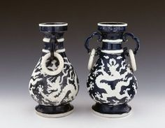 A pair of porcelain vases with ring handles decorated in biscuit and gilding on a blue ground. The shape of these vases derives from that of an ancient or archaistic bronze vessel, a 'hu', for storing wine. Each has a rounded body, narrowing neck with two applied horizontal bands and a dish mouth. The side handles are shaped like the outline of a 'ruyi' cloud with a free-moving ring suspended from each. Unusually the circular base is flat and fully glazed. 271mm tall, 1522-1566, Ming dynasty