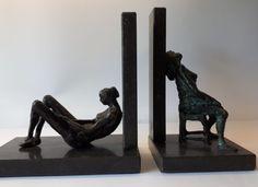 Naakte vrouw onderuit  gezakt en op stoel (brons). Bruikbaar als boeksensteun. Bronze nude bookends.