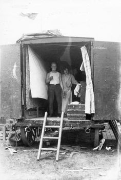 """""""A man and a woman, in the process of getting dressed for a circus performance, pose informally in the back of a circus wagon."""""""