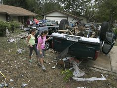 Sisters Briana Arriaga, right, and Angelina Arriaga look over their father's truck that was found several houses down the block and overturned in a neighbor's front lawn in the Thoroughbred Farms subdivision near Elroy, Texas. Nearby Dry Creek overflowed, engulfing their homes, and sent debris downstream.  Ralph Barrera, Austin American-Statesman via AP