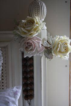 Pink and white faux roses around the french caned headboard.