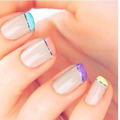 Fantásticas uñas en color beige decoradas con las puntas de colores, en azul celeste, naranja, morado y amarillo adornadas con una fina línea plateada.