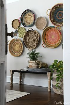 This colorful, boho, African basket gallery wall is an unexpected way to display art! She found affordable, hand woven baskets at HomeGoods along with woven bench to create a unique wall. Baskets from Ghana add color and personality to the gray walls in this dining room and see her unique way of hanging baskets. kellyelko.com sponsored pin #gallerywall #baskets #art