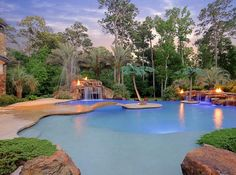 "Lagoon-style pool with large shallow ""beach"" area, arched bridge to island jumping platform, built-in in-pool booth with bench, waterfalls, multiple fire pits, grotto with spa, spray deck for the kids, and more..."