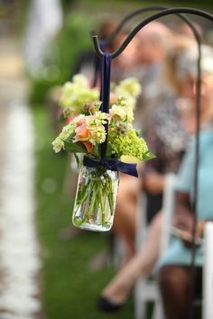 Each aisle in this Charleston wedding ceremony gets a Navy Blue & Pink Aisle decoration made from Mason jars and fresh flowers.