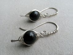 Beautiful black obsidian sterling silver earrings. They were made with 8mm round smooth gemstones wrapped in herringbone style with sterling silver wire. They hang on handmade, wire wrapped sterling silver earwires. They were hammered and hand polished for more style and depth. OBSIDIAN is truth-enhancing. A strongly protective stone, it forms a shield against negativity. It blocks psychic attack and absorbs negative energies from the environment. Obsidian draws out mental stress and…
