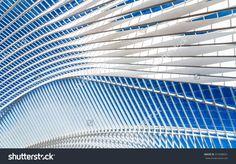 Прозрачный потолок в современной железнодорожной станции с голубое небо на фоне…