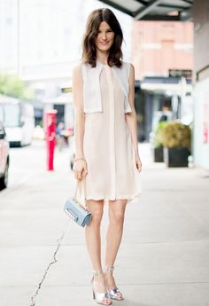 Hanneli Mustaparta wears a pink and white shift dress, pastel blue Valentino bag, and silver sandals