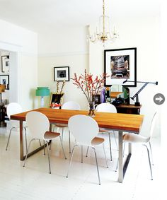 """Elana avoids the """"matchy matchy"""" look by mixing materials. Her dining room features wood, stainless steel, crystal, glossy whites, and fresh flowers."""