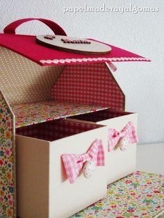 Una casita hecha con cartonaje y varios apartados de almacenamiento.