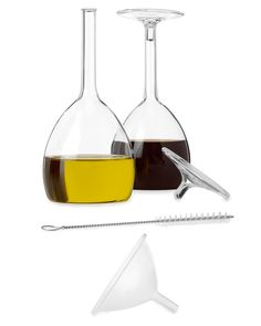 No, you're not imagining things. Those goblets of red and white wine that appear to be standing on their heads are actually clever cruets for holding olive oil and vinegar. Pour the liquids through the delicate stems to dress your salad, and cap them off with their glass base. The set of two includes a funnel for easy filling, and a brush for cleaning. Made in China. $35