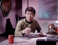 Sulu eats trayed snack as brought to him in the botany lab by Yeoman Rand