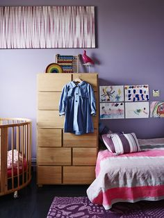 Rosie and Silke's shared bedroom.  Wall hanging made by Trudy from silk purchased in Laos, artwork by Rosie (5 yrs).  Stokke cot. Oak Chest of Drawers by Habitat (UK).  Pink pigeon light by Ed Carpenter. Girls raincoat by Hucklebones London.  Bonnie and Neil linen on bed.  Photo - Eve Wilson, production – Lucy Feagins / The Design Files.
