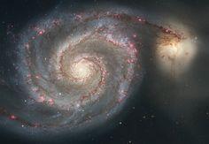 """Imagem feita pelo telescópio Hubble mostra a galáxia em espiral M51, conhecida como Whirlpool. As curvas sinuosas são formadas por estrelas, gás e poeira. À primeira vista, parece que uma galáxia menor, à direita, está puxando um dos """"braços"""" da M51. Mas uma interpretação da imagem dá conta que a galáxia menor está passando por trás da Whirlpool"""