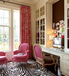 Pink and chocolate brown home office with built-in desk accented with crystal hardware below glass front cabinets on either side of a chocolate brown pinboard behind the computer. A French Bergere chair stands below the desk with a pink back and brown seat trimmed with pink piping over a black and white zebra print rug. A pair of pink slipcovered arm chairs stand below the tall traditional windows which are dressed in floor length ivory and pink damask drapes.