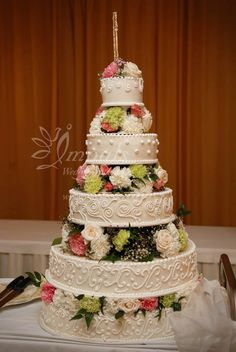 5-tiers wedding cake with fresh flowers and fire works at the top.