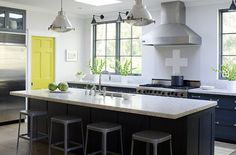 Rob Karosis Kitchens and Baths did this one.  Love all windows instead of upper cabinets.  The floating hood and pendant lights are great.  Bright pop of color from the door is lovely.