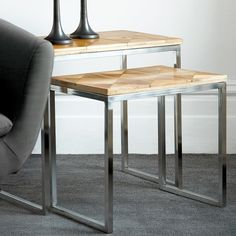 These side tables feature rich wood surfaces with etched, geometric patterns and complementary stainless-steel legs.