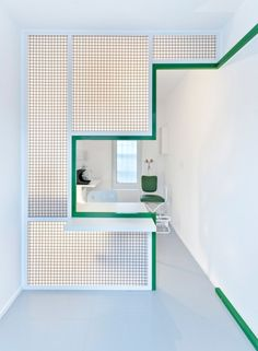 A stepped cut-out in the mesh partition forms a customer service window in this denture repair centre by Polish architect Adam Wiercinski.