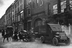 Circa 1922: Uniformed Free State troops fire an 18 pounder field gun from the top of Henry Street, Dublin at Republican targets in the Gresham hotel, during the Irish Civil War. A Lancia armoured car is in the foreground.