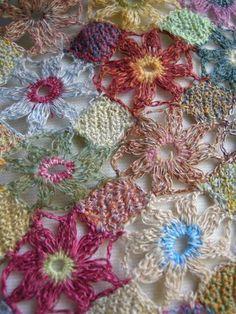 Gehäkelter Schal aus vielen verschiedenen kleinen bunten Häkelblumen