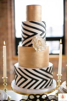 Striking wedding cake design idea - gold, black, white, flower accent
