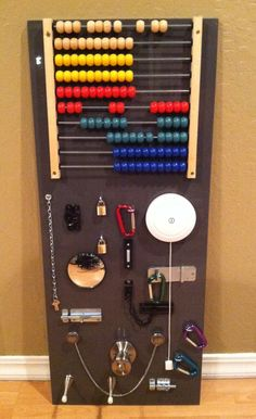 """A children's homemade """"busy board."""" This started with an Ikea As-Is cabinet door for only 5 dollars, add an abacus and a few fine-motor gadgets & its endless fun!"""