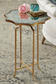 Like something from a Fitzgerald novel, our mirror-top accent table is the epitome of sleek transitional style. Its modern angular legs are forged iron with a hand-gilded, variegated brass finish. The starburst-shaped, smoked mirror top is inset and has all the cool cachet of a Left Bank bibliothèque.