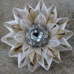 Beige Flower Corsage  Handmade from beige and ivory ribbons, this unique corsage pin features a silver rhinestone center.   This beige flower pin is 3 inches wide with felt backing and brooch pin attached.  A beautiful flower pin for hats, lapels or special occasions.   Each pin is packag...