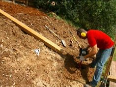 HGTV Gardens shows you how to build an easy retaining wall from pressure-treated lumber. Retaining Wall Drainage, Wooden Retaining Wall, Backyard Retaining Walls, Building A Retaining Wall, Fire Pit Backyard, Patio, Fresco, Wooden Pergola Kits, Timber Posts