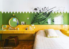 Esse quarto de casal tem parede verde e cabeceira e penteadeira de madeira.