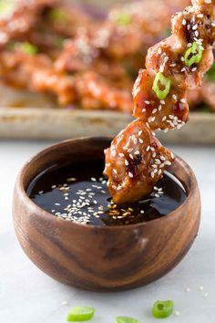 Dipping a grilled chicken skewer into a wooden bowl of Japanese yakitori sauce