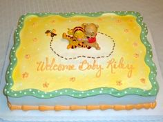 green, yellow, and white whinnie the pooh and tigger baby shower cake