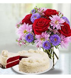 Beautiful arrangement of red roses, purple waxflower, lavender daisy poms, myrtle in a clear glass vase and also includes two rich layers of red chocolate cake, fill and covered with the finest, pure cream cheese frosting, and then garnished with white chocolate sprinkles around the sides.