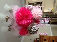 Tissue balls hanging from light fixture.  Added curling ribbon and tulle to hide the ties holding everything up.  Baby shower theme was leopard print and pink.