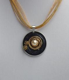 Handgefertigter Anhänger aus schwarzen Nespressokapseln, verziert mit einer goldfarbenen Metallspirale, einer Perle und kleinen goldfarbenen Metallblümchen. Beidseitig sauber verarbeitet....