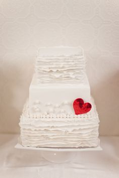 White ruffly wedding cake with red sequin heart