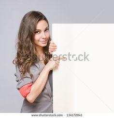 Beautiful elegant young businesswoman holding large blank white sign. - stock photo
