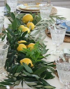 Layer fresh herbs down the center of the table  and finish off with a few lemons placed on top of the  fragrant herbs.