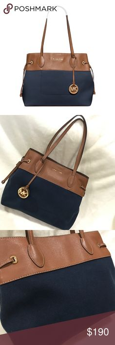 """🌟HP🌟👜 MK Blue Marina Large Canvas Tote Beautiful handbag in navy blue woven canvas & brown pebbled leather trim with gold tone hardware. This handbag features a dangling cut out MK logo medallion, 1 main open pocket with magnetic snap closure, 1 Interior zipper pocket, 4 interior slip pockets & 2 shoulder straps with 10-1/2"""" drop. Dimensions: 11-1/2''  H x 13.5'' W x 5.5'' D.  Excellent conditions, no flaws.  🚭/pet 🆓home 📫Same day shipping 💲Offers welcome!!💲 Michael Kors Bags…"""