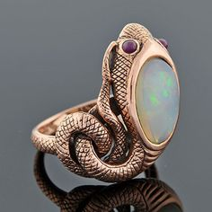 """This fabulous snake ring is from the Art Nouveau (ca1910) era and is simply marvelous. Coiling around ones finger, the snake's body is made of 9kt rose gold and represents the mounting as well as the band of the ring. The head of the snake is decorated with a single cabochon opal which is oval in shape and two rubies represent its eyes. It has stunning detail and textured, scale-like etching throughout. Of English origin, the shank has several hallmarks including a crown and """"375""""."""