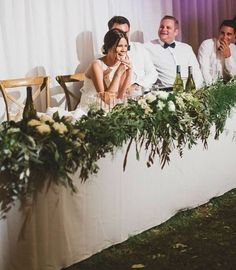 The front of the table will be covered with a runner of cameilia foliage, green nagi, Italian ruscus, and seeded eucalyptus with clusters of ivory spray roses, purple lilacs, and dark purple hellebore mixed into the greenery infront of the bride and groom; with scattered gold votives going down the length of the tables