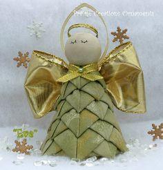 Eva es un hermoso angelito hecho de una tela verde salvia luz con patrón de copo de nieve blanco y oro. Sus toques de halo, alas y cinta son