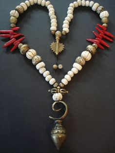 'Whitefire'. Round & melon sacred conch shell beads from Nepal, shell prayer beads carved with OM, African bronze basket & brass flower beads, 2 large Khmer gold lac over wax melon beads, large coral spike beads, a bronze handmade Naga India bead hangs at the back of the necklace, and the crowning glory, a bronze Dorje and a heavy old Kalimantan bronze earring used as a pendant.