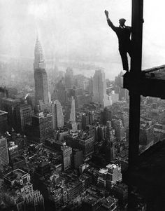 man waves from Empire State Building construction site 1930