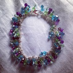 Purple blue & green clear glass beaded charm bracelet on silver chain!   Price: £8  Warning: Please keep this bracelet dry at all times! Do not wear it in the shower or continuous water use!