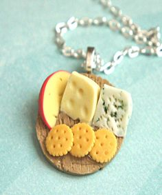 This necklace features a plate of handmade cheese and crackers made from polymer clay. The plate pendant measures 3 cm in diameter and is securely attached to a silver tone chain necklace that measure