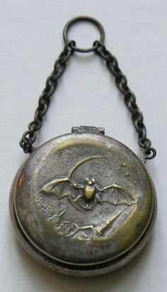 Victorian Bat and Quarter Moon Chatelaine Piece. This chatelaine piece features a bat flying over a town with a quarter moon in the background. The chatelaine piece could have functioned to hold rouge or coins